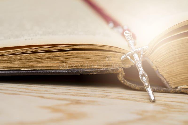 Incrocio sulla bibbia su un fondo di legno Libro sacro immagine stock