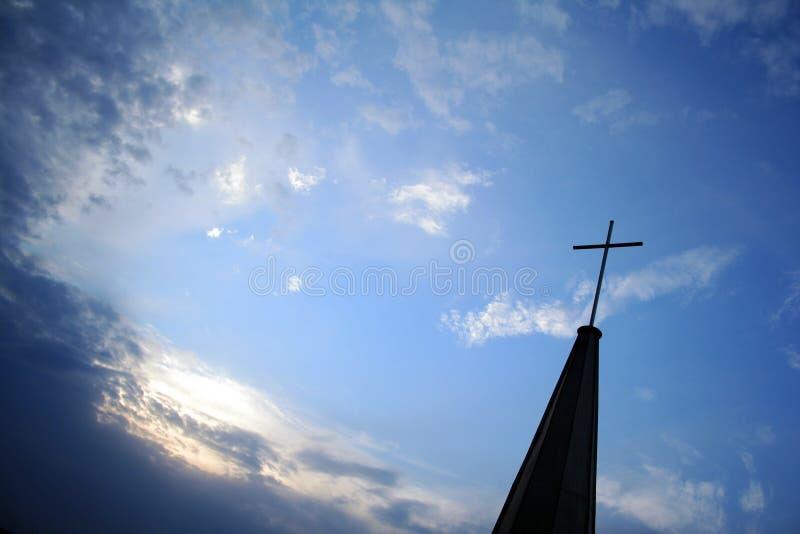 Incrocio superiore della chiesa protestante nel cielo immagini stock