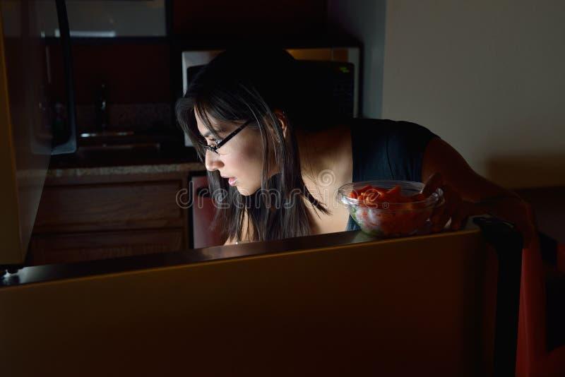 Incursión hispánica joven del refrigerador de la noche de la mujer en casa - foto de archivo libre de regalías