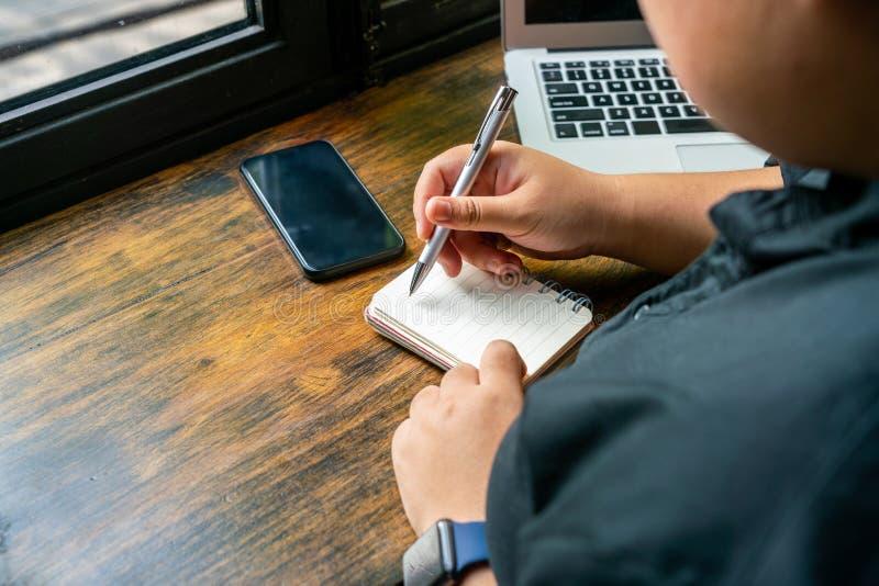 Indépendant écrivant le carnet quotidien à côté de l'ordinateur et du téléphone portable photos stock