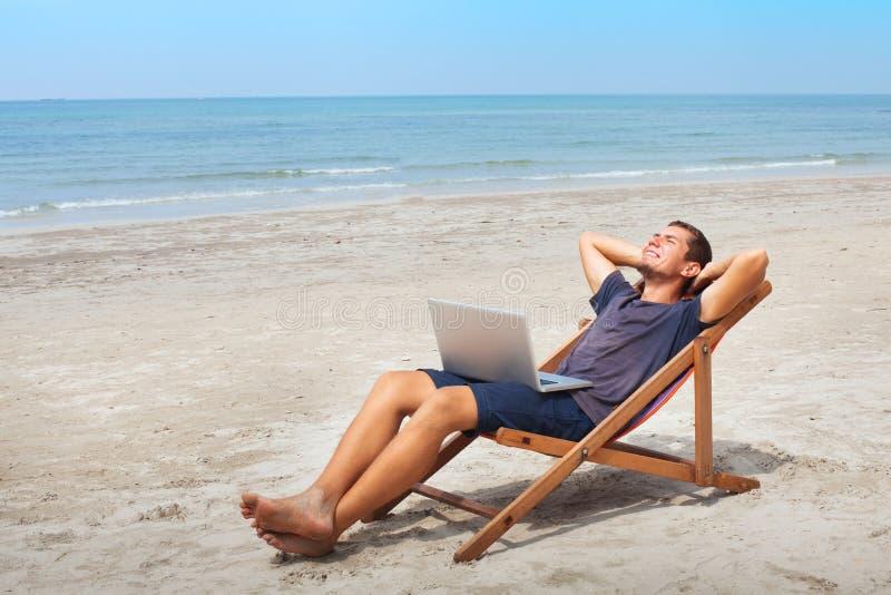 Indépendant avec l'ordinateur portable sur la plage, détente heureuse réussie d'homme d'affaires images stock