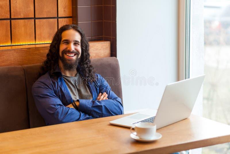 Indépendant barbu bel satisfait de jeune homme dans le style occasionnel se reposant en café avec l'ordinateur portable, les bras image libre de droits