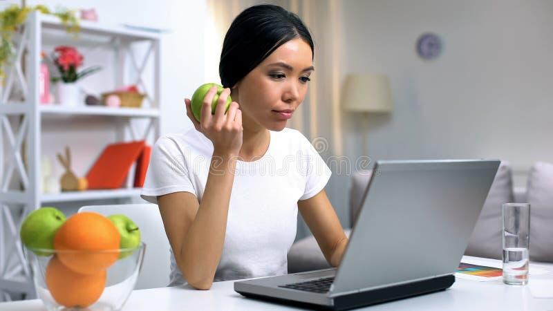 Indépendant féminin dans le projet en ligne de fonctionnement blanc de T-shirt tenant la pomme fraîche photo libre de droits