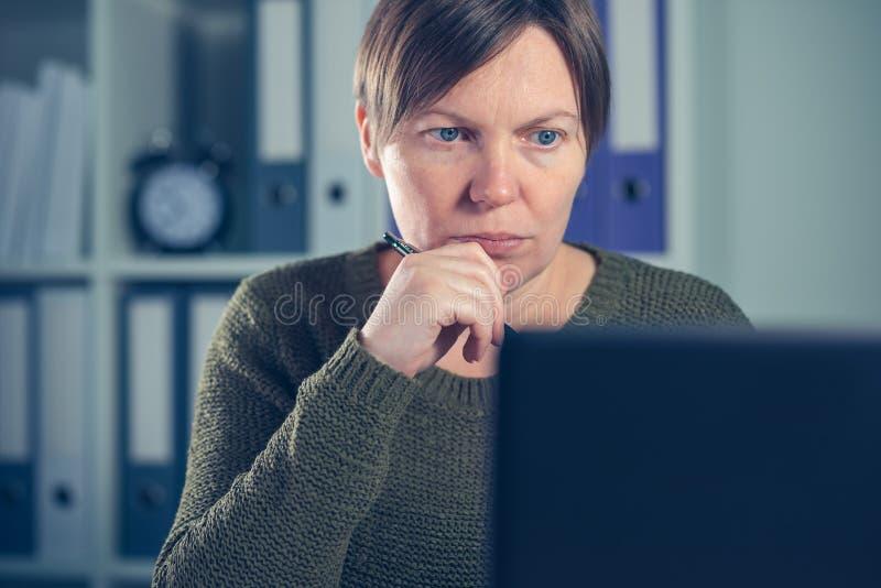 Indépendant féminin sérieux travaillant sur l'ordinateur portable photo stock