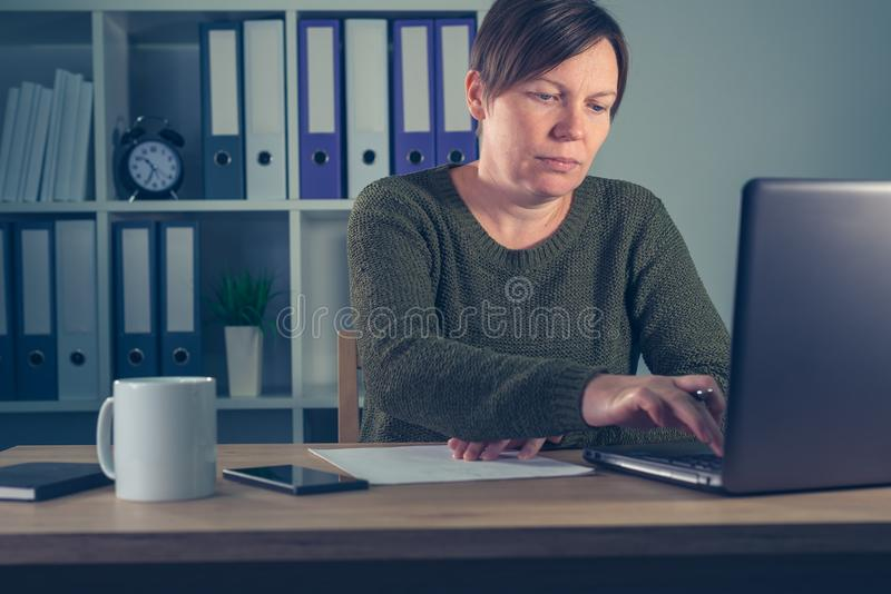 Indépendant féminin travaillant des heures supplémentaires dans le siège social photographie stock