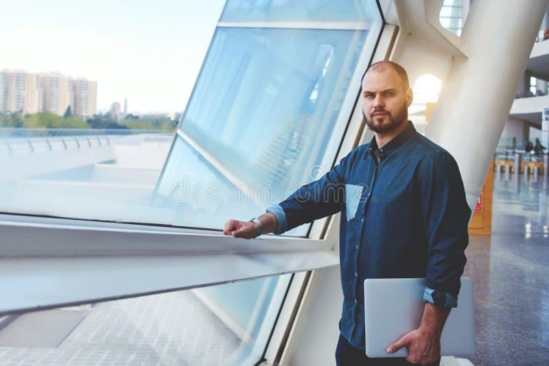 Indépendant masculin réussi posant dans l'intérieur moderne après présentation sur l'ordinateur portable photo libre de droits