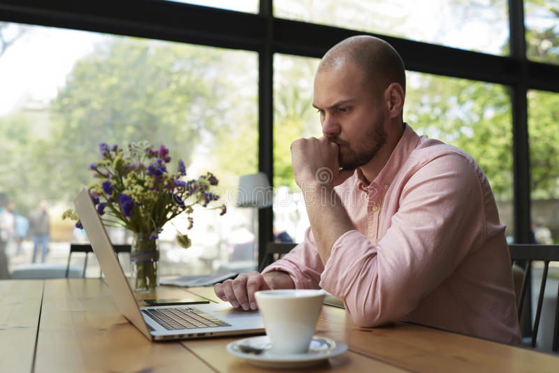Indépendant masculin se reliant à la radio par l'intermédiaire de l'ordinateur portable photo stock