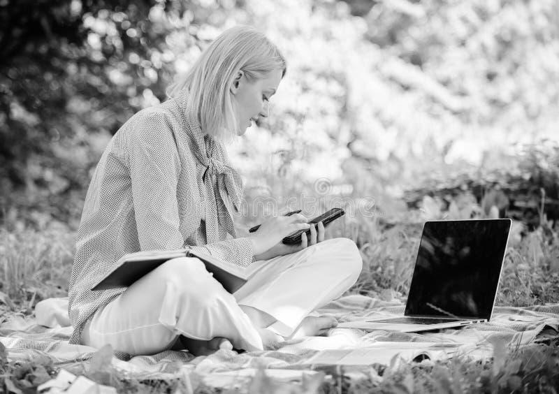 Indépendant réussi devenu Extérieur de gestion d'affaires La femme avec l'ordinateur portable reposent le pré d'herbe Dame d'affa photographie stock