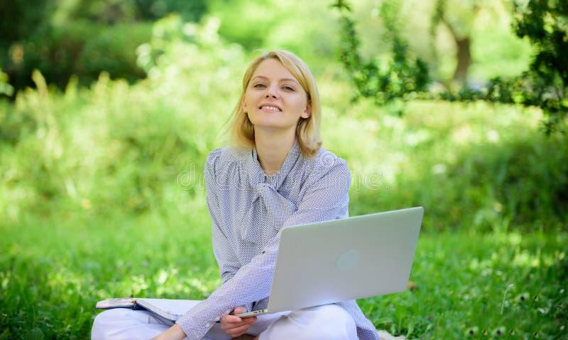 Indépendant réussi devenu La femme avec l'ordinateur portable s'asseyent sur le pré d'herbe de couverture Concept indépendant en  photo libre de droits