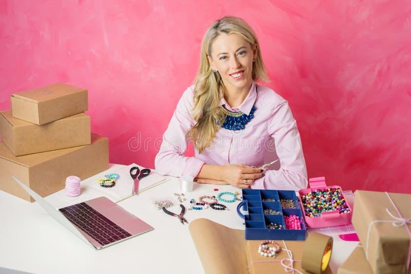 Indépendant travaillant de la maison Femme faisant des bijoux et vendant des marchandises en ligne images libres de droits