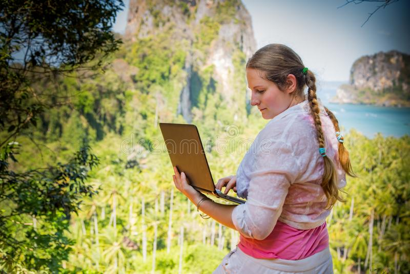 Indépendante de jeune femme dans le fonctionnement blanc avec l'ordinateur portable sur un dessus de la montagne avec la vue sur  image stock
