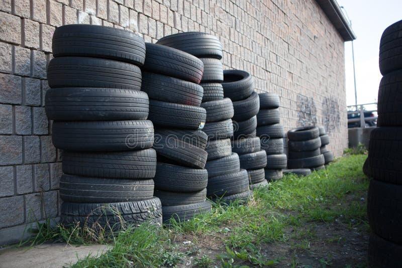A indústria de borracha empilhou pneus usados contra a parede de tijolo fotografia de stock royalty free