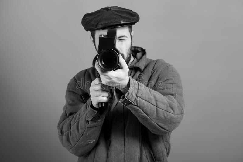 Indústria do cinema da ideia Operador cinematográfico com a câmera retro em suas mãos, tiro do estúdio, efeito monocromático Home imagem de stock royalty free