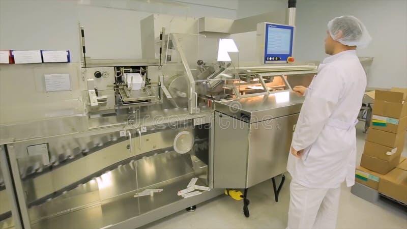 Indústria farmacêutica Operário masculino que inspeciona a qualidade dos comprimidos que empacotam na fábrica farmacêutica automá imagem de stock royalty free