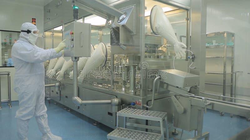 Indústria farmacêutica Operário masculino que inspeciona a qualidade dos comprimidos que empacotam na fábrica farmacêutica automá foto de stock royalty free