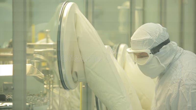 Indústria farmacêutica Operário masculino que inspeciona a qualidade dos comprimidos que empacotam na fábrica farmacêutica automá imagens de stock