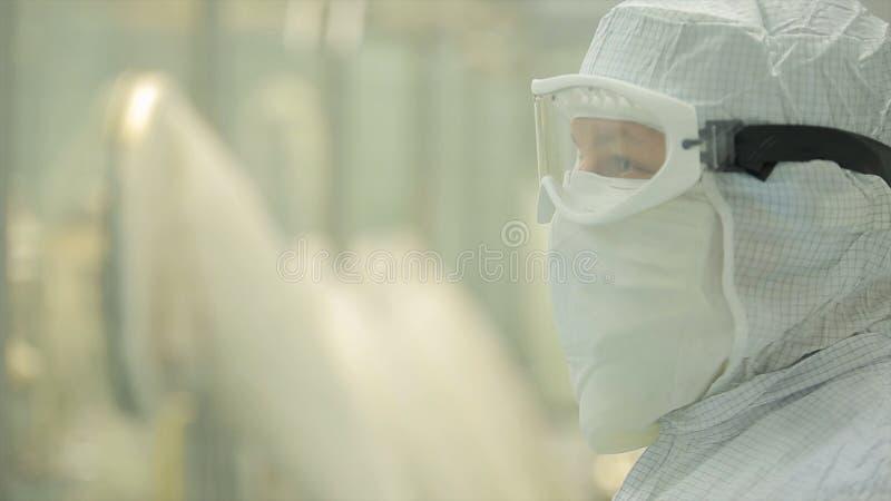 Indústria farmacêutica Operário masculino que inspeciona a qualidade dos comprimidos que empacotam na fábrica farmacêutica automá fotografia de stock royalty free