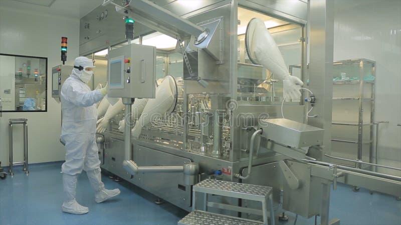 Indústria farmacêutica Operário masculino que inspeciona a qualidade dos comprimidos que empacotam na fábrica farmacêutica automá fotos de stock