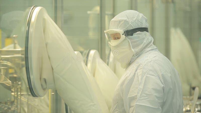 Indústria farmacêutica Operário masculino que inspeciona a qualidade dos comprimidos que empacotam na fábrica farmacêutica automá imagens de stock royalty free