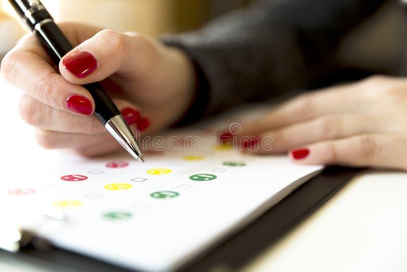 Indagine di valutazione di servizio di assistenza al cliente con i fronti sorridente e la penna immagine stock