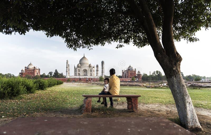 INDE 2016 D'ÂGRÂ : Deux garçons s'asseyant sous l'arbre et appréciant la vue étonnante de Taj Mahal, Âgrâ, Inde photo stock