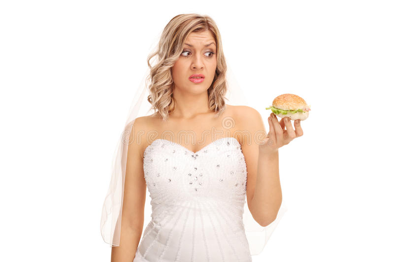 Indecisive bride looking at a sandwich royalty free stock images