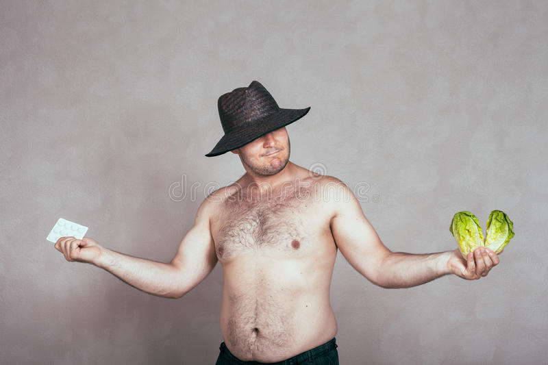 Indecisive naked corpulent man with pharmaceuticals and vegetable. Indecisive naked corpulent man in hat holding pharmaceutical products and lettuce stock photos