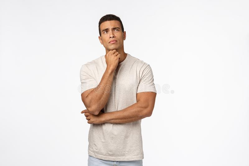 Indecisive young thoughtful male athlete trying make hard choice, decide what do, touching chin, looking up troubled stock photography