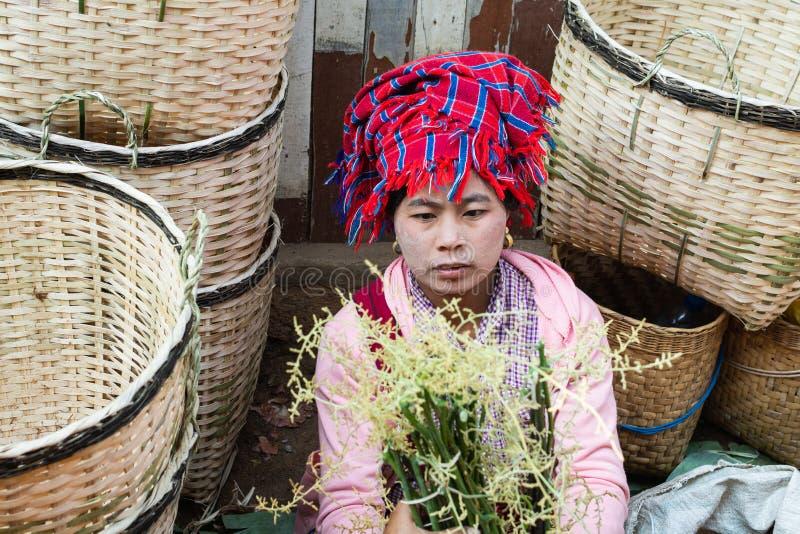 Indein, Myanmar - March 2019: Burmese woman sells bamboo baskets on the street market. Indein, Myanmar - March 2019: Burmese woman from Pao dragon tribe sells stock image