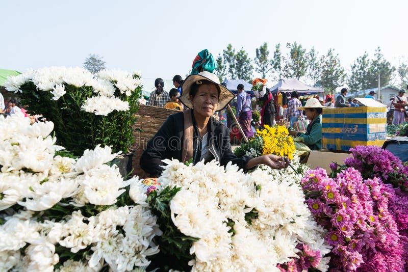 Indein, Myanmar - March 2019: Burmese woman sells chrysanthemum flowers on the street market royalty free stock photos