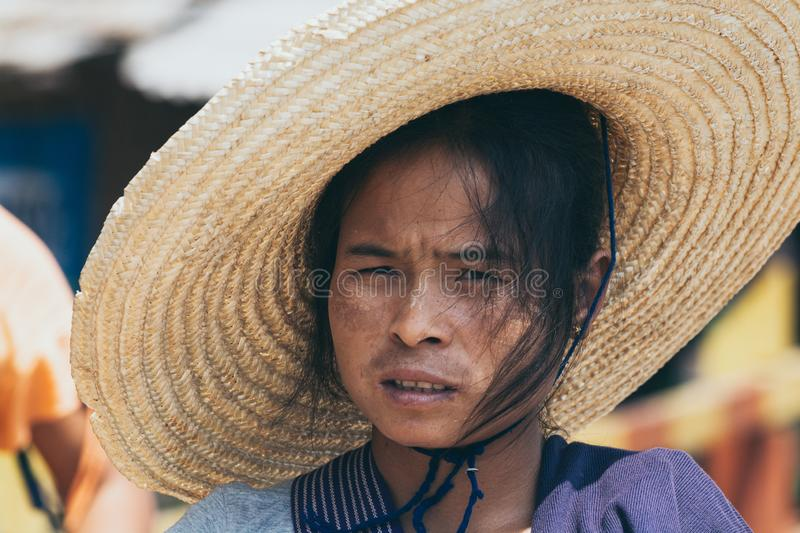 Indein, Myanmar - March 2019: portrait of a young Burmese woman in a big straw hat royalty free stock photo