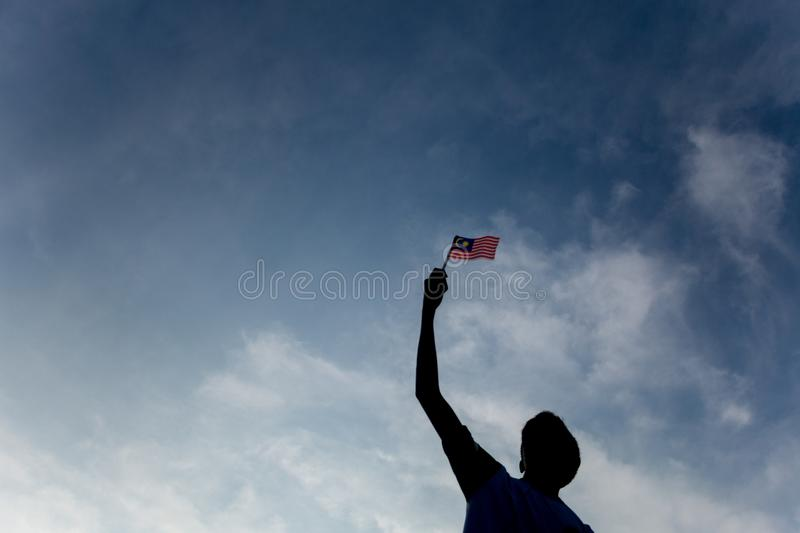 Independence Day concept. A happy and proud citizen holding Malaysian flag. stock image