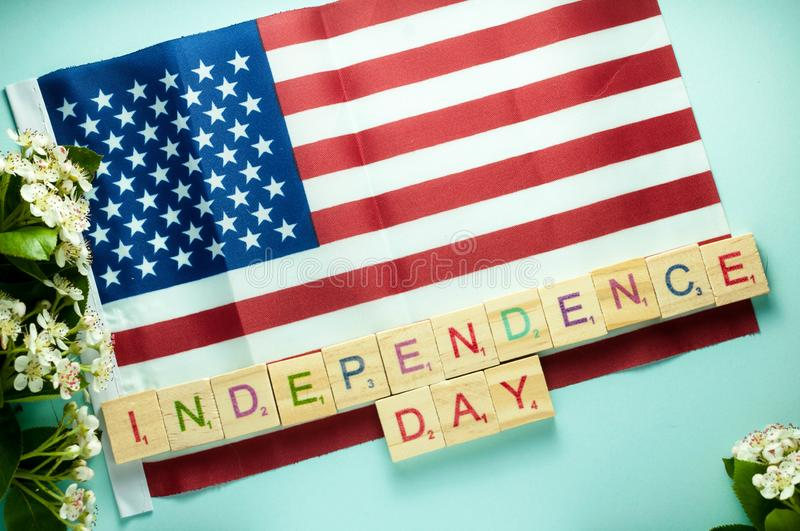 independence day lettering with wooden cubes and laid out on American flag royalty free stock image