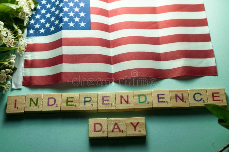 Independence day lettering on wooden cubes under American flag and near blooming branches royalty free stock photo
