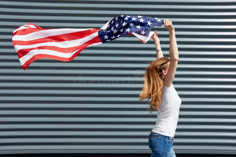 Independence day and patriotic concept. Active girl with long ginger hair running with waved by wind USA flag, holding it above. royalty free stock photos