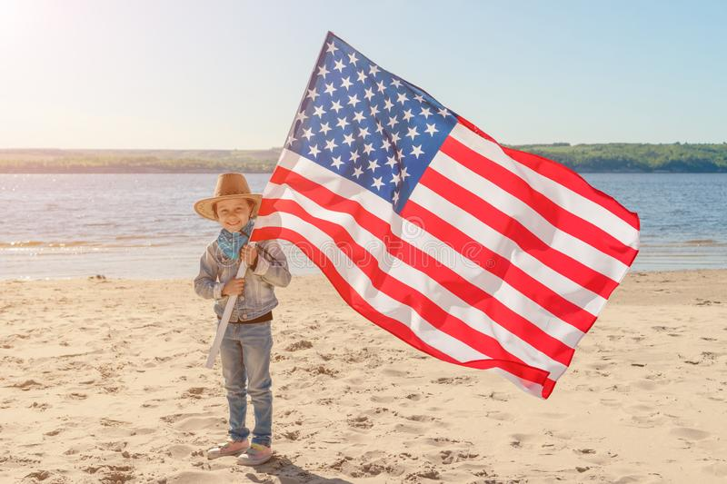Beautiful happy girl with green eyes with American flag on a bright sunny day. A girl in a cowboy hat and denim jacket stock photo