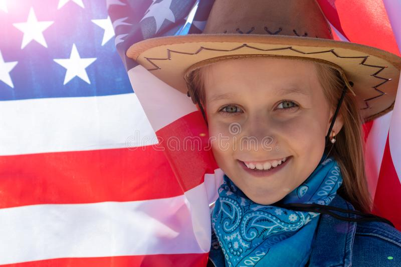 Ndependence Day. Beautiful happy girl with green eyes on the background of the American flag on a bright sunny day. A girl in a stock photography