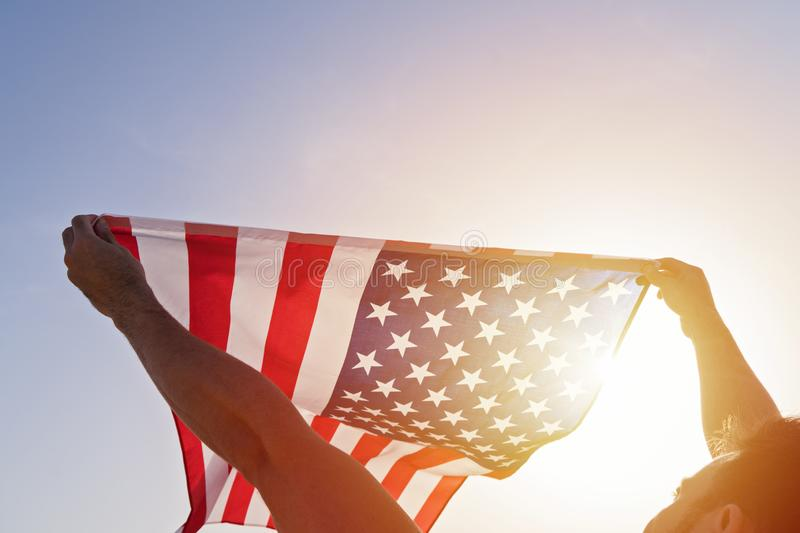 Man`s raised hands with waving American Flag against clear blue sky stock photos