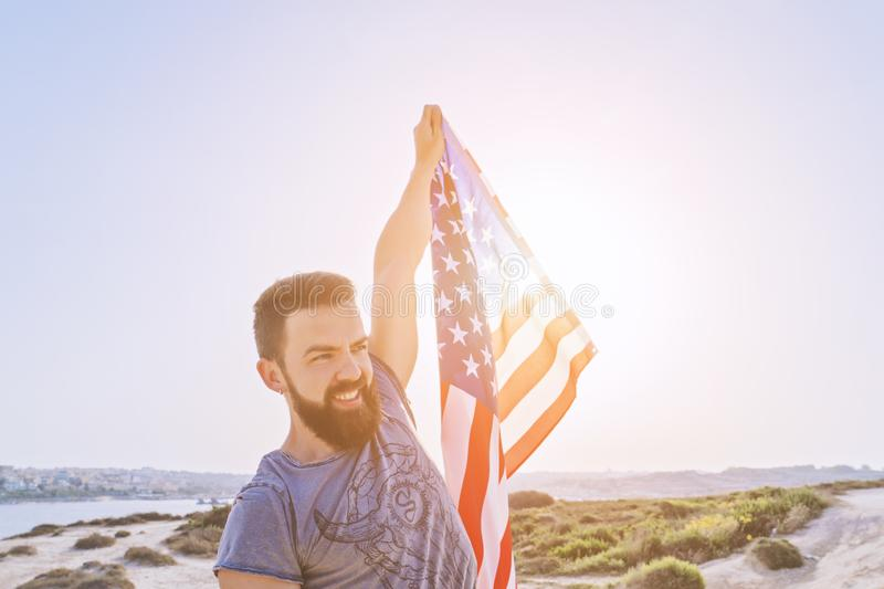 Smiling bearded man holding in raised hand American Flag royalty free stock photos