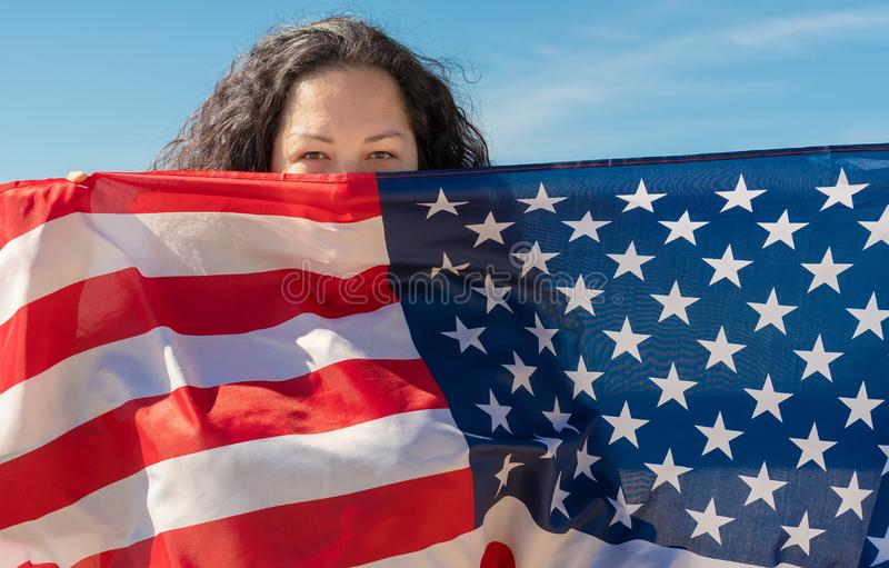 Independence Day. A woman with black curly hair is holding an American flag. The concept of world peace royalty free stock image