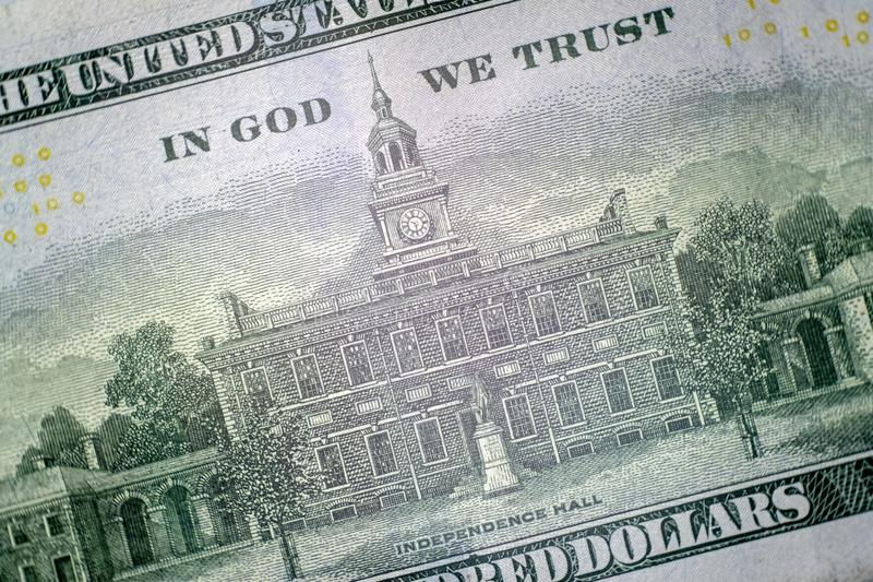 Macro. Independence Hall building and the inscription IN GOD WE TRUST on the reverse side of the US hundred dollar bill. Close-up stock photo