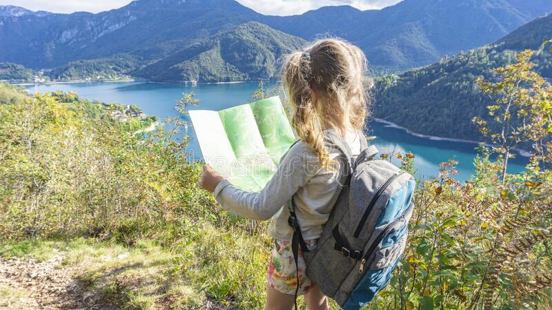An independent blonde girl with a tourist backpack lays a route on a map on the shore of a mountain lake in the Italian Alps. An cute independent blonde girl royalty free stock photos
