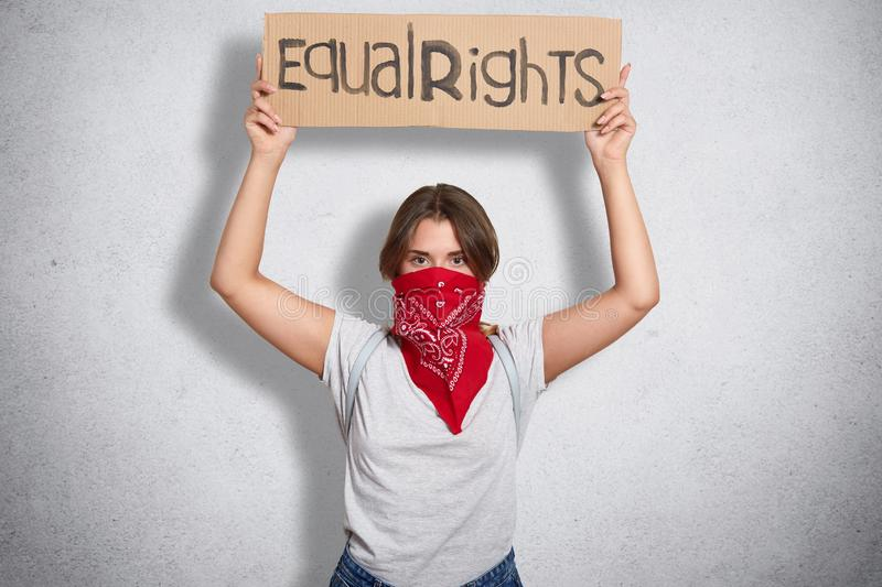 Independent confident young feminist standing  over grey background in studio, raising her hands, holding sign equal. Rights, looking for support and stock image