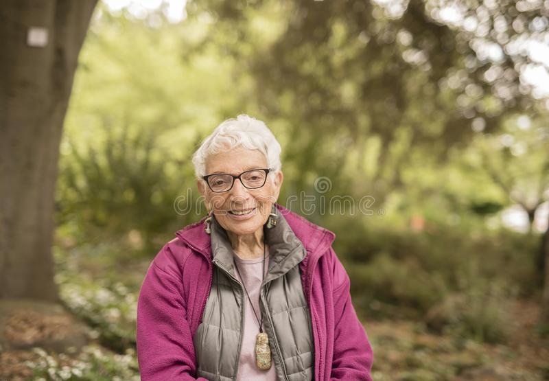 Independent Elderly Woman in the Park Sitting on Bench stock photos