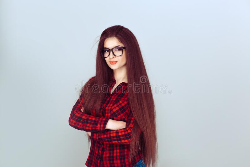 Independent girl. Confident smiling attractive young redhead woman with folded arms wearing glasses standing against light blue royalty free stock image