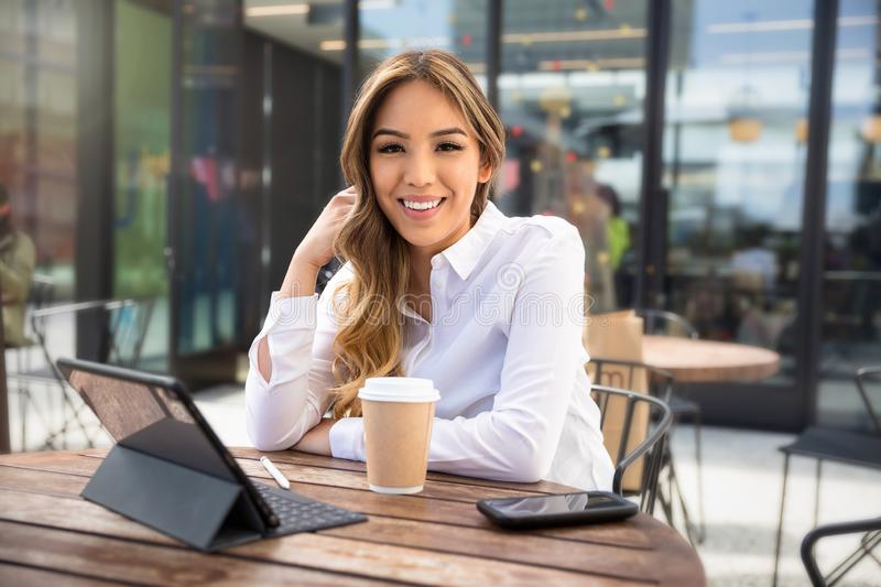 Independent multiethnic female entrepreneur, web business owner, young self-employed professional working from laptop at coffee sh royalty free stock photography