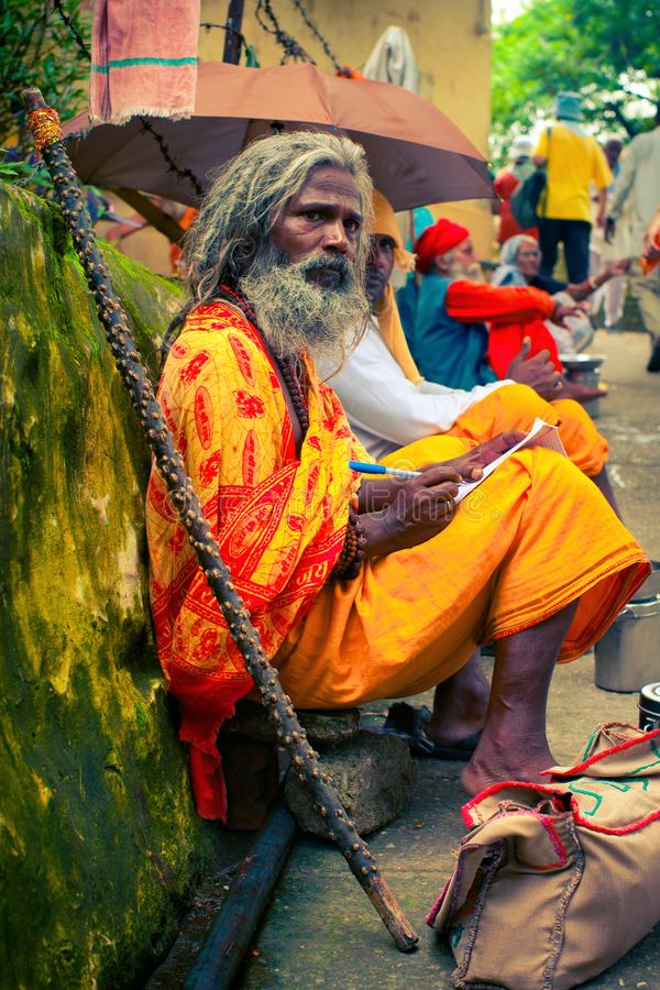Inder Sadhu sitzt an der Seite der Straße und notiert seine Gedanken im Notizbuch lizenzfreie stockbilder
