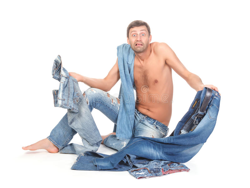 Indesicive man trying to dress. Attractive Indecisive man trying to dress sitting shirtless and barefoot on the floor holding several pairs of denim jeans royalty free stock photos