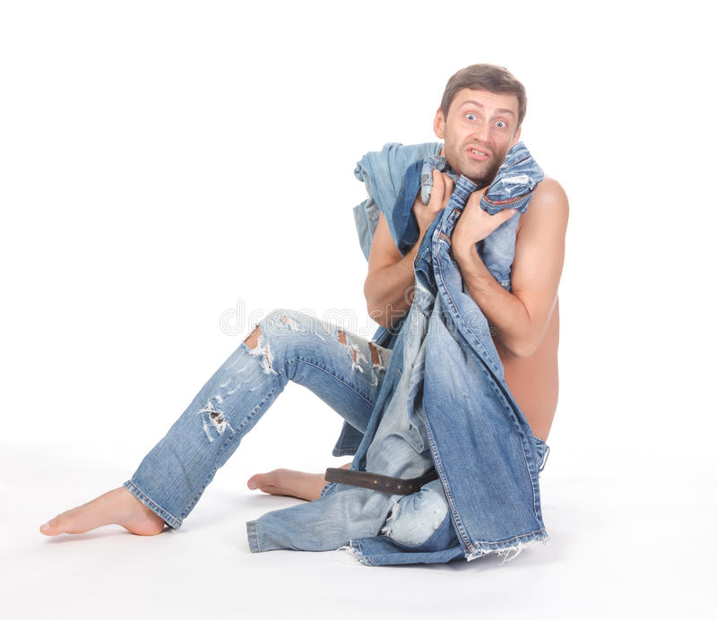Indesicive man trying to dress. Attractive Indecisive man trying to dress sitting shirtless and barefoot on the floor holding several pairs of denim jeans royalty free stock photography