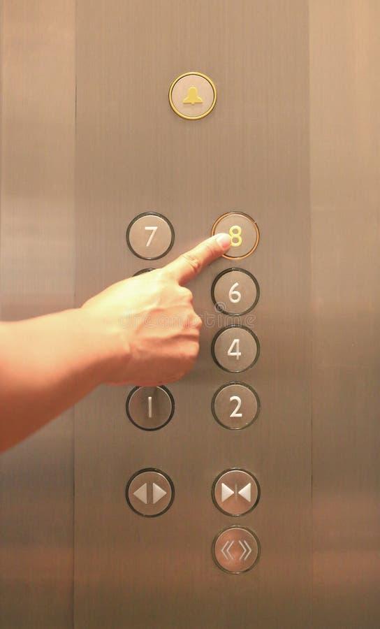 Index appuyant sur le huitième bouton de plancher dans l'ascenseur images libres de droits